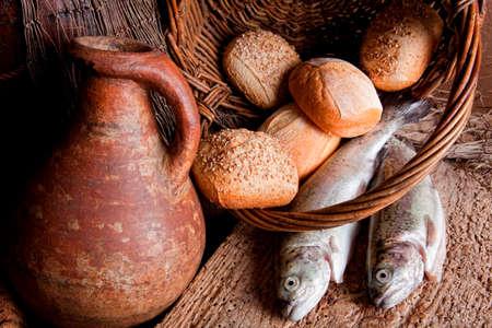 bread and wine: Vino, panes y pescado fresco en una vieja canasta