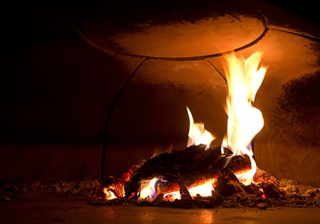 Hot look inside a pizza oven, with the fire burning photo