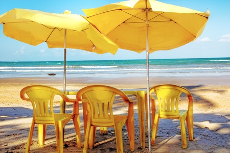 sunshades: View at the beach, sitting  behind threee yellow chairs, a  tables and two sunshades