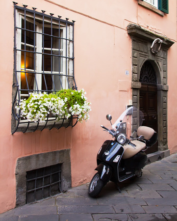 quickness: An Vespa on the street in front of an house in Italy. Tipical scene in most of the cities. Stock Photo