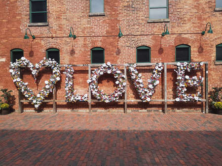 Toronto, Ontario / Canada - September 18, 2019: A LOVE sign with a heart, made of colourful locks put on by people and flower on a wooden structure in front of a red brick wall in Distillery District.