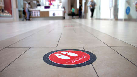 A red sticker in a Canadian Mall warning to stand here to respect covid-19 distancing rules. Focus on the sticker, blurred background. Stock Photo