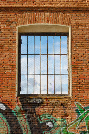 window graffiti: window in brick wall with graffiti from the sky looks Stock Photo