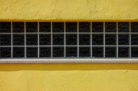 tabellare: una vetrata allungata in forma tabellare su un muro giallo Archivio Fotografico