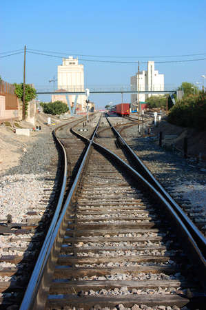 parallels: train tracks with a bridge and a background station Stock Photo
