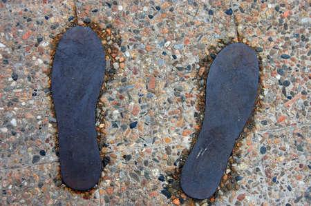 piso piedra: siluetas de calzado de bronce en suelo de piedra