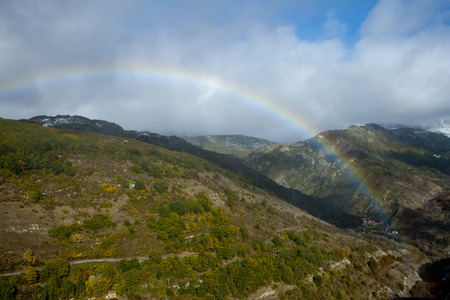 Rainbow in a mountainous landscape with beech forests.