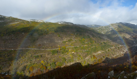Whole rainbow in a mountainous landscape with beech forests. Banco de Imagens - 120659068
