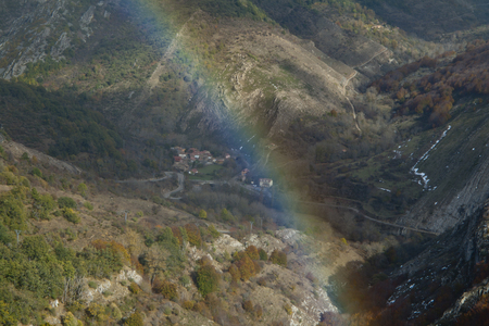 Rainbow closeup in a mountainous landscape with beech forests. Фото со стока
