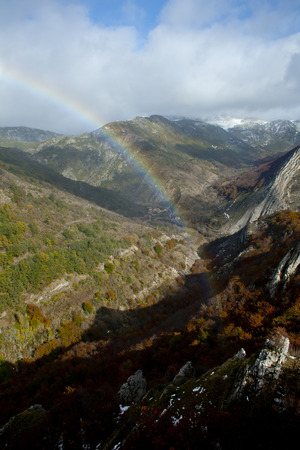 half rainbow in a mountainous landscape with beech forests. Banco de Imagens