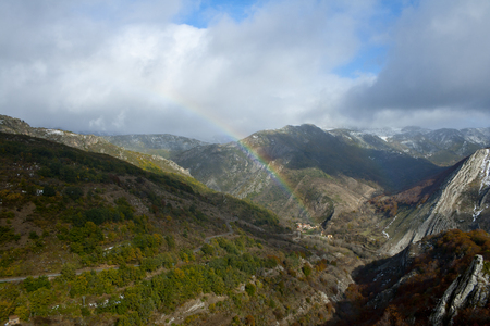mountainous landscape with beech forests and a rainbow.