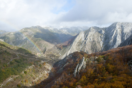 mountainous landscape and rainbow with beech forests. Banco de Imagens