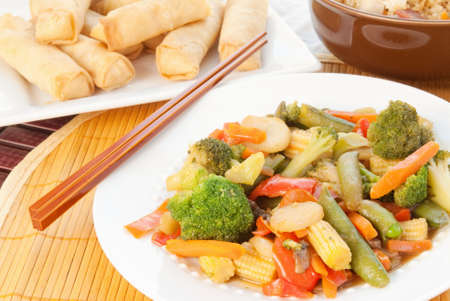 Asian stir fry with broccoli, sugar snap peas, carrots, water chestnuts, red peppers, baby cob corn, and mushrooms in a tangy ginger sesame sauce  Shrimp spring rolls and chicken fried rice in the background   Stock Photo