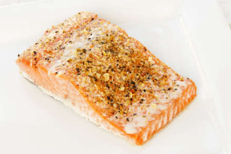 Baked Alaskan Sockeye salmon covered with lemon pepper seasoning blend  Served on a white plate with an antique linen tablecloth in the background