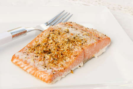 Baked Alaskan sockeye salmon with lemon pepper herbs garnished on top. Served on a white plate with an antique linen tablecloth in background. Shallow DOF and selective focus. Adobe RGB color profile.