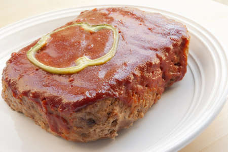 meat loaf: meat loaf topped with a green bell pepper slice and a ketchup based sauce. Shallow DOF.  Stock Photo