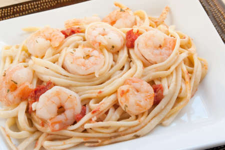 Shrimp scampi made with linguini, diced tomatoes, butter, garlic, parsley and herbs. Served on stacked white and brown plates. Shot in natural light. Selective focus with shallow DOF. Stock Photo
