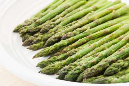 Organic roasted asparagus sprinkled with salt, pepper, garlic and other herbs served in a white plate. Shot in natural light. Selective focus with shallow DOF.