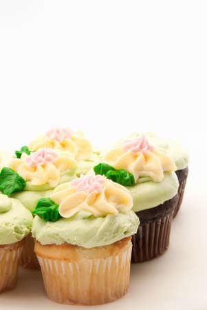 chocolate and yellow cupcakes made with butter cream frosting in pastel colors.