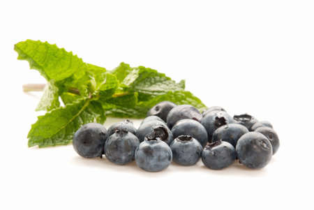 Organic blueberries with a sprig of mint in the background. Selective focus with shallow DOF.  Stock Photo