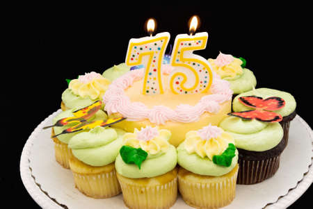 Birthday cake with pastel colored butter cream icing surrounded by yellow and chocolate cupcakes. A 75 candle is burning.