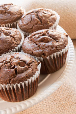 semisweet: Homemade chocolate cinnamon muffins made with semi-sweet chocolate candies and ground cinnamon. Shallow DOF and focus on the muffin in the front. Shot in natural light. Stock Photo