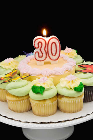 Birthday cake surrounded by cupcakes with a burning 30 candle.  photo