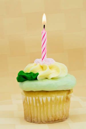 Cupcake with one candle burning in front of a yellow textured background. Icing is butter cream. Cupcake is yellow.