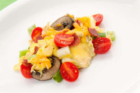 turkey bacon: Scrambled eggs healthy breakfast made with eggs, grape tomatoes, mushroom, turkey bacon and spring onions served on a white plate.