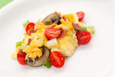 turkey bacon: Uova strapazzate sana colazione a base di uova, pomodori uva, funghi, pancetta di tacchino e cipolline servito su un piatto bianco.