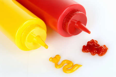 Mustard and ketchup plastic bottles lying on their side with matching ingredients. Stock Photo
