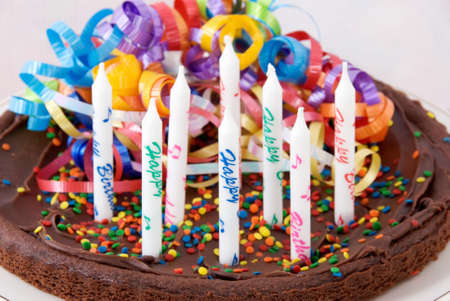 Brownie birthday cake with eight unlit candles that say Happy Birthday on them. Selective focus on the front candles. Stock Photo - 17700884
