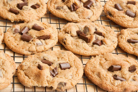 chocolate chip cookies right out of the oven onto a cooling rack. Stock Photo - 17700892