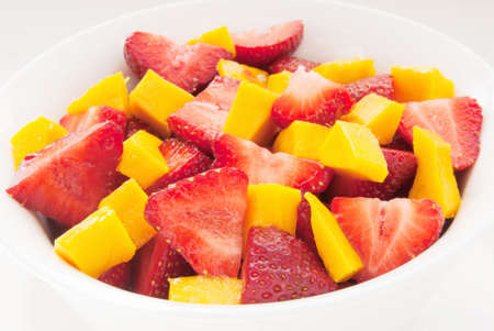 Fruit salad made with Strawberry and mango. served in a white bowl with a white background.