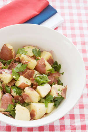 turkey bacon: healthful potato salad made with new potatoes, turkey bacon, and Italian Leaf Parsley with a fresh vinaigrette dressing. Red white and blue napkins in the background.