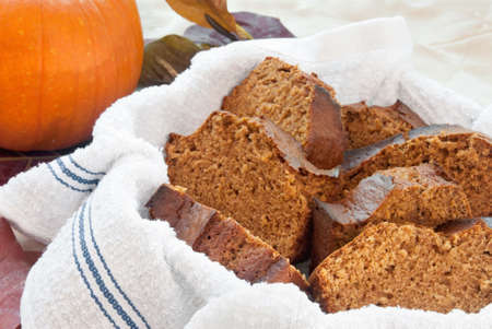 pumpkin spice bread served in a clean, new dish towel. Fresh pumpkin in the background.