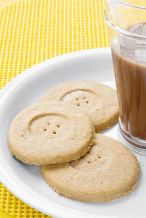 chocolate cookies served with milk. The center of the cookie has a button hole look. Light chocolate.