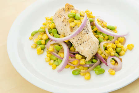 grilled chicken with corn, edamame and red onion. sprinkled with black pepper and cooked in olive oil. Stock Photo