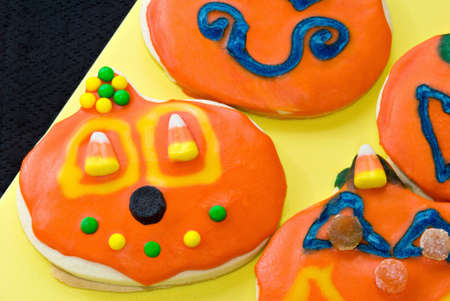 Halloween sugar cookies shaped like pumpkins. Homemade. Covered with sprinkles, candy corn, gum drops and assorted icings.  photo