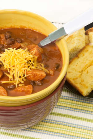 cornbread: chili made with black beans and polksa sausage with a serving of homemade yellow cornbread. Stacked bowls.