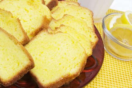Lemon cake serviced with lemons and a glass of milk. Stock Photo