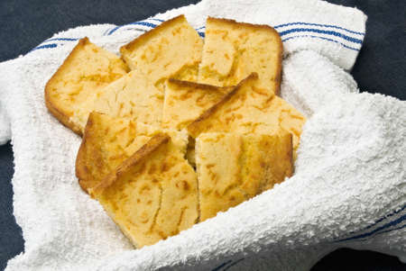 homemade cornbread served on a clean new dish towel. Dark blue denim fabric background. Stock Photo