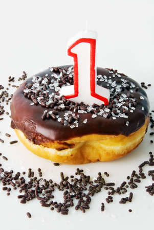 Glazed chocolate donut covered with sprinkles. Topped off with an unlit number one candle.  Stock Photo