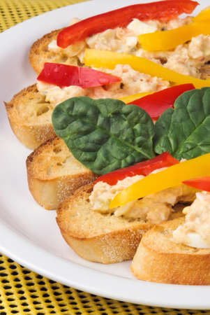 albacore tuna and wild pink salmon open faced sandwiches. Garnished with red and yellow bell peppers and spinach leaves. All on top of toasted baguettes.