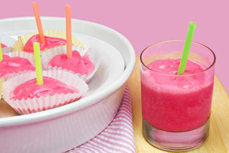 raspberry frozen sherbert sorbet ice cream treats served pop style with straws for easy eating.