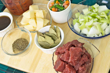 Beef soup raw ingredients. Includes red trimmed beef stew meat, celery and onion, frozen mixed vegetables, cubed potatoes, bay leaves, spices and herbs, beef broth and diced tomatoes.