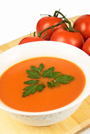 Tomato soup garnished with Italian parsley and slicing tomatoes in the background. Stock Photo