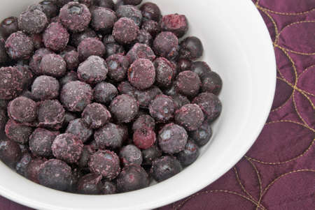 frozen blueberries served in a white bowl with a purple place mat. Ice crystals on fruit.