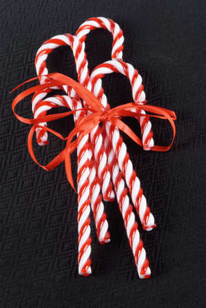 candy canes tied up with a satin ribbon all on a black textured background.