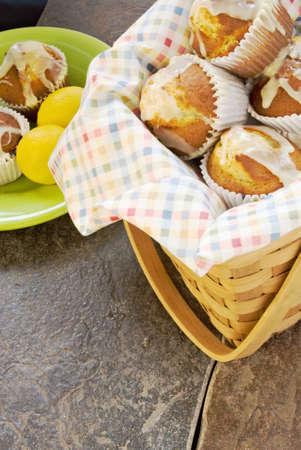 muffins lemon poppy seed in a wicker picnic basket on ceramic tile.